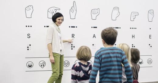 Eine Museumsführerin im Foyer der Ausstellung Sprache. An der Wand steht das Wort Sprache in Fingeralphabet, Morsealphabet, lateinischen Buchstaben, Brailleschrift und Emojis. Die Frau ziegt auf den Buchstaben R. Vor ihr stehen vier Kinder.