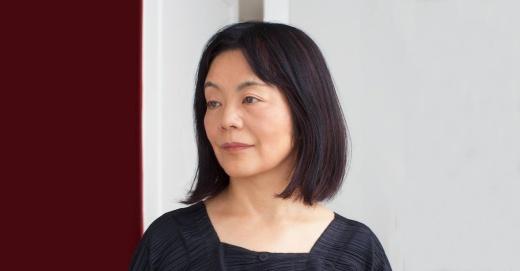 Porträt von Yoko Tawada mit dunklen Haaren und dunkler Kleidung. Sie blickt nach links.