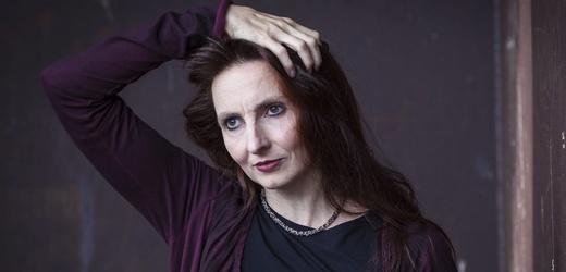 Porträt von Katja Erfurth. Die Frau mittleren Alters ist schwarz gekleidet und fährt sich durch die dunklen Haare. Sie blickt nach links.